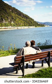 An elderly couple is sitting on a bench by the river and looking for the beautiful view. Image has a vintage effect applied.