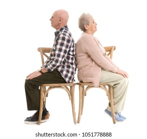 Elderly couple sitting on chairs against white background