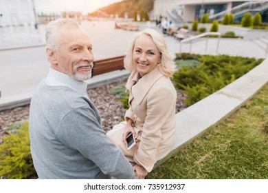 An elderly couple is sitting on the edge of a flower bed. They smile tenderly at each other