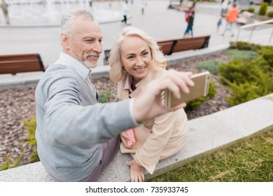 An elderly couple is sitting on the edge of a flower bed. They do selfie on a smartphone. Behind the square there are people