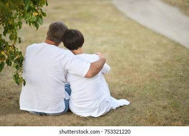 elderly couple sitting on nature and looking into the distance