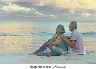 Elderly couple sitting on the shore and looks at sea