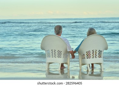 Elderly couple sitting on the shore and looking at each other