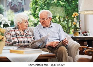 Älteres Ehepaar sitzt zu Hause auf dem Sofa mit Tageszeitung und Tee