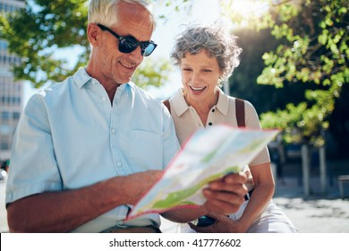 Elderly couple sitting outdoors and using city map. Happy retired couple looking for a destination on a city map.