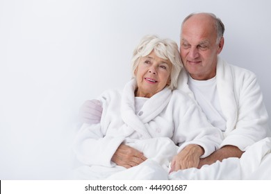 Elderly couple is sitting snuggled relaxed in bed in the morning