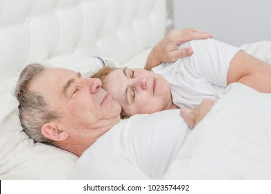 elderly couple sleeping together on the bed