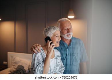 Elderly couple standing by the window, woman talking o the phone
