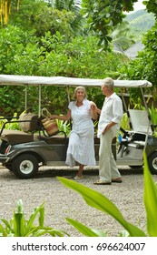 Elderly couple standing near cart