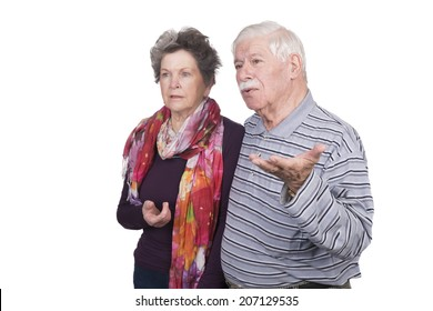 Elderly couple standing with question marks on their faces