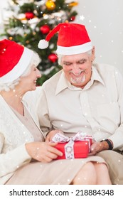 Elderly couple swapping christmas presents against twinkling stars