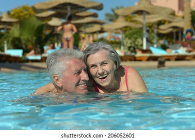 Elderly couple swimming in pool at hotel resort