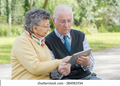 elderly couple with a tablet in the park
