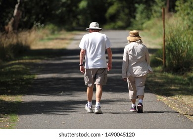 Elderly couple taking a walk in a park on a sunny day.
