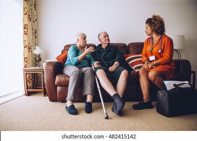 Elderly couple talking to their healthcare worker at home. They are sittig on the sofa in the living room.