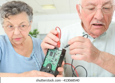 Elderly couple testing computer hard drive with multimeter