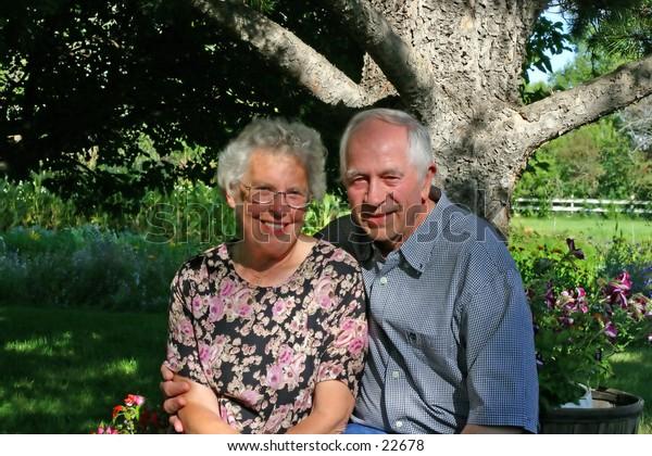 An elderly couple, in their backyard.