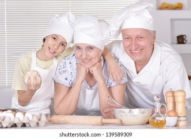 an elderly couple and their grandson knead the dough for the pie together