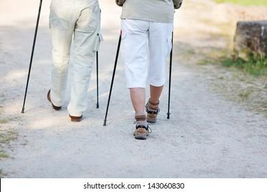 Elderly couple traveling with nordic walking sticks, walking together.