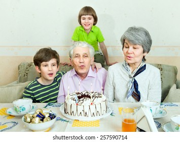 an elderly couple with two grandchildren blow out the candles on the cake