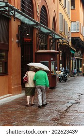 elderly couple with an umbrella on a street in Bologna