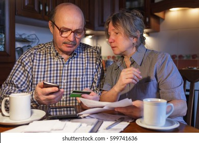 An elderly couple uses electronic payments through a smartphone and a bank card. They are afraid of fraud and an unfamiliar system of payment.