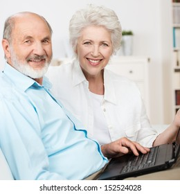 Elderly couple using a laptop computer as they sit side by side on a couch sharing the internet and smiling at the camera