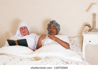 Elderly couple in vintage clothing reading and knitting in bed