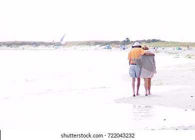 An elderly couple walk along the sandy beach holding each other. he photograph is taken behind them of the man and woman walking away. Their arms are around each other. Woman wearing dress.