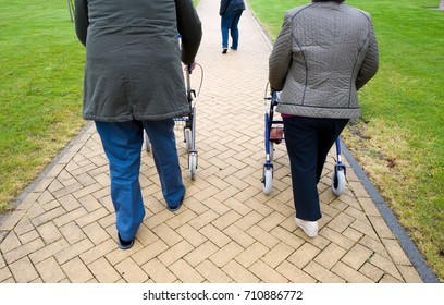 An elderly couple walking behind their walking frames