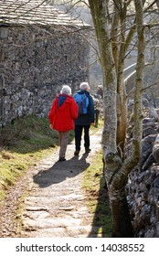 Elderly couple walking in country lane in Grassington, Yorkshire.