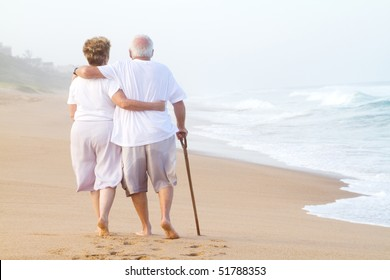 elderly couple walking on beach