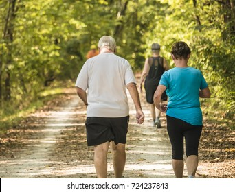 Elderly couple walking on a trail for exercise; woods on the sides of the trail; man is overweight