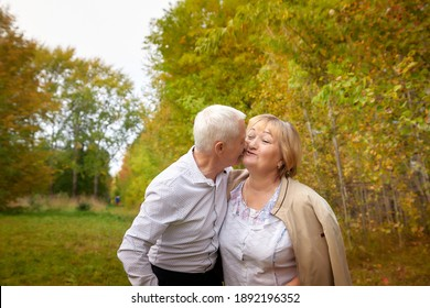 Elderly couple walking in the park on an autumn day