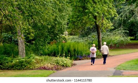 Elderly couple walking in the Royal Botanical Gardens in Edinburgh,  public gardens and a scientific centre for plant study. Edinburgh, Scotland uK.  July 2018