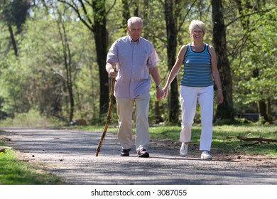 Elderly couple walking through the parc hand in hand