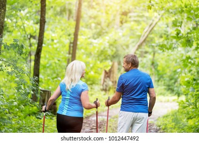 Elderly couple walking together in the forest. Retirement activities. Fitness lifestyle.