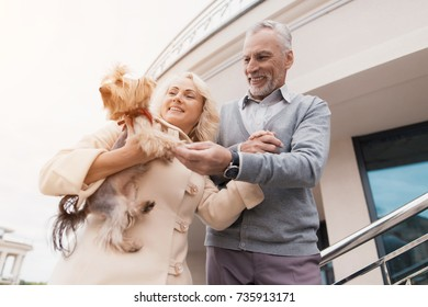 An elderly couple is walking. A woman has a dog in her arms. The man is walking beside him. They smile happily.