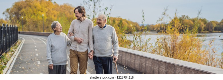 An elderly couple walks in the park with a male assistant or adult grandson. Caring for the elderly, volunteering BANNER, LONG FORMAT