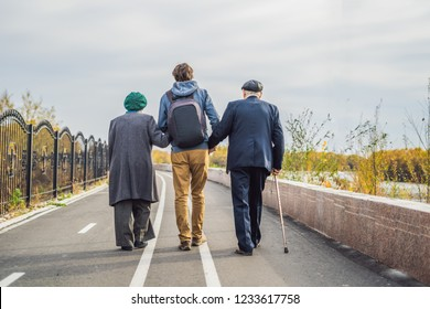 An elderly couple walks in the park with a male assistant or adult grandson. Caring for the elderly, volunteering