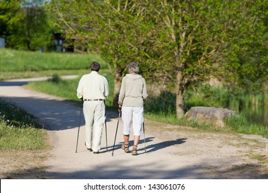 Elderly couple wandering with nordic walking sticks inside the park together.