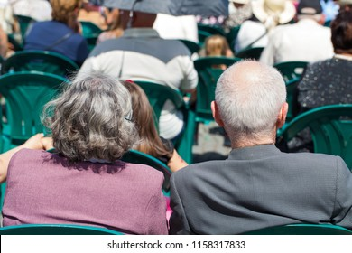 Elderly couple watching an outdoor show in the city center, Cluj-Napoca