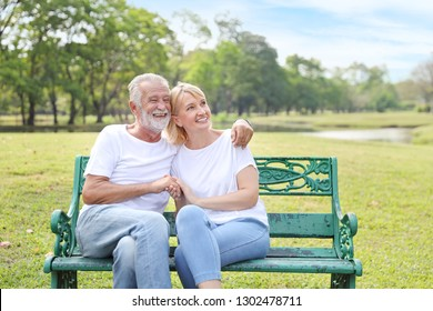 elderly couple with white shirt and blue jean sitting and embracing in park during summer time on wedding anniversary day