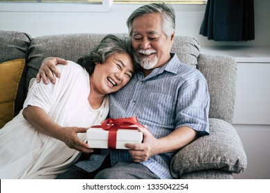 Elderly Couples Surprise and gift box at living room