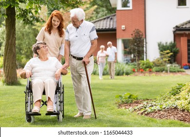 An elderly disabled couple with their caretaker in the garden outside of a private rehabilitation clinic.