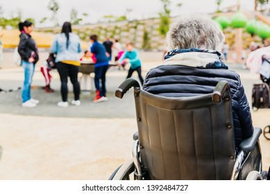 Elderly disabled woman sitting back to back in a wheelchair in a playground.