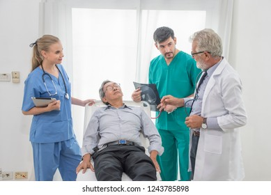 Elderly Doctor with group doctor assistant ,nurse , and senior patient are discussing something at hospital, Healthcare workers concep