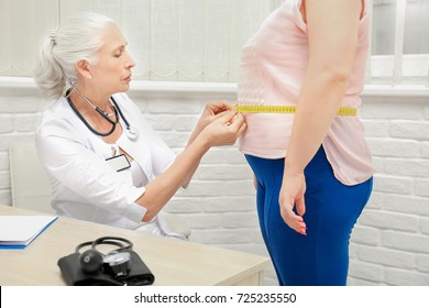 Elderly doctor measuring waist of overweight woman in hospital