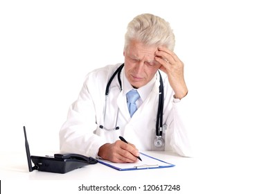 elderly doctor at a table on a white