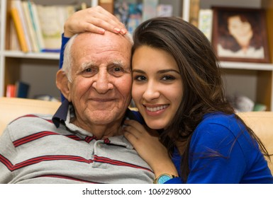 Elderly eighty plus year old man with granddaughter in a home setting.